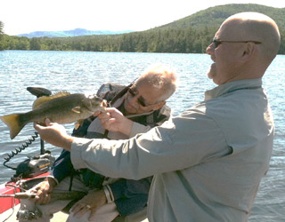 Fish NH Guide Servce clent Malini and her father with a nice largemouth bass caught on Lake Winnipesaukee
